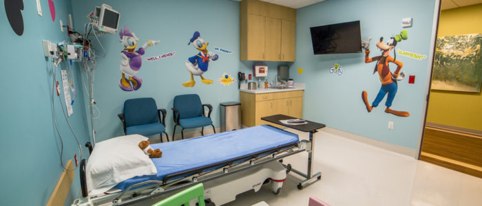 pediatric room with table and cartoons at emergency center