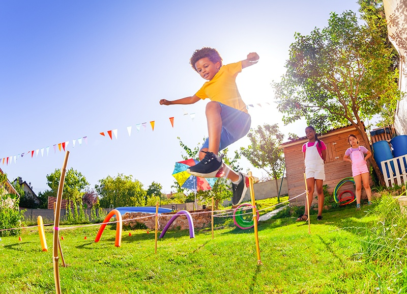 little boy jumping in the air, going through backyard obstacle course