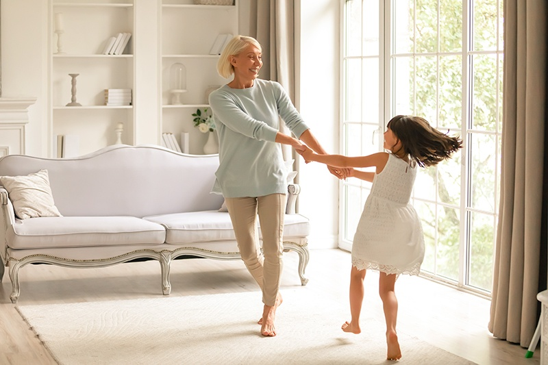 Little girl with her mom dancing together in the living room