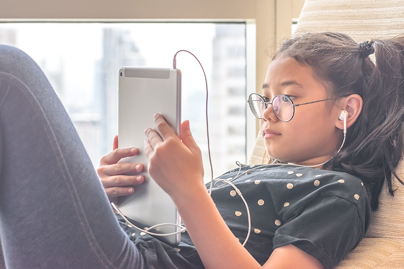 young girl wearing glasses, sitting on windowsill watching tablet