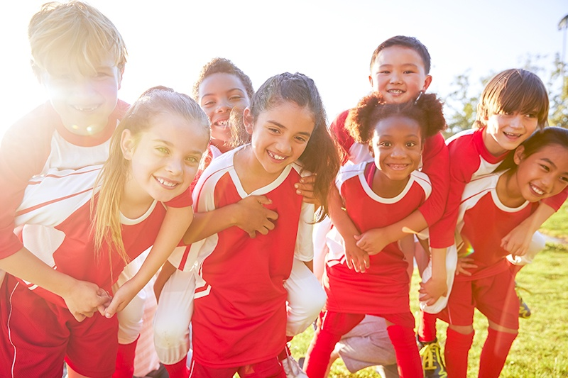 group of kids hunched together in red jerseys after sports