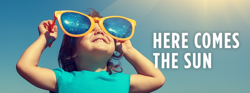 Here comes the sun, happy child standing outside in the sunshine with large sunglasses on